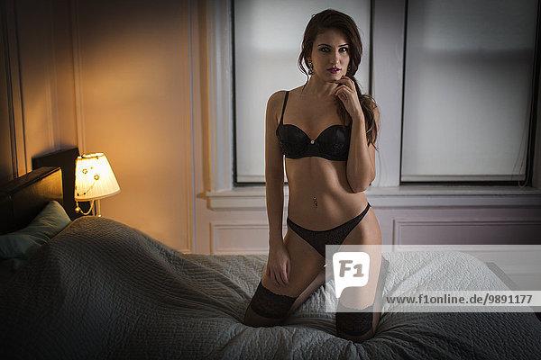 Frau kniend Bett Unterwäsche