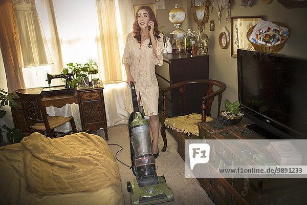 Woman vacuuming in vintage dress