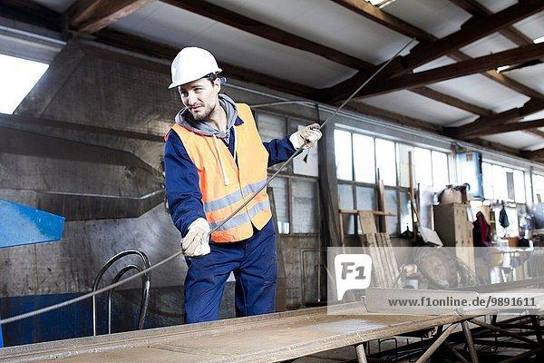 Fabrikarbeiter bewegt Stahlstab im Betonbewehrungswerk
