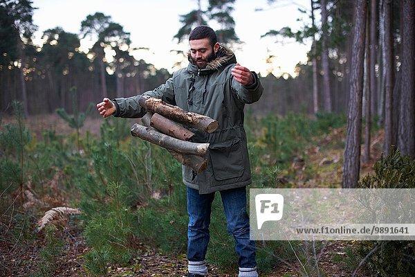 Junger Mann lässt Holz für das Lagerfeuer im Wald fallen.