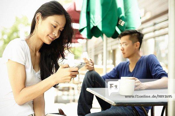Touristenpaar im Straßencafé mit Smartphones  The Bund  Shanghai  China