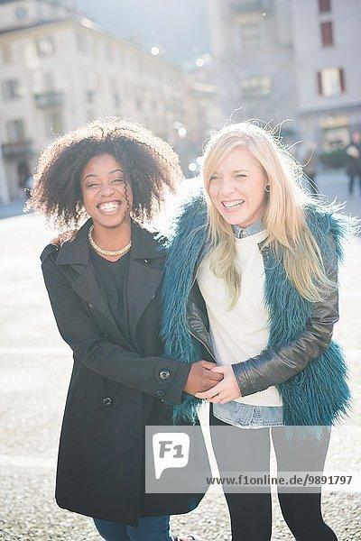 Porträt von zwei Freundinnen  die auf dem Marktplatz lachen