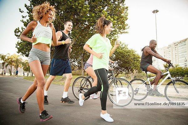 Erwachsene Freunde beim Radfahren und Laufen im Park
