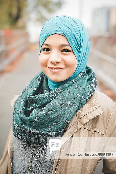 Portrait of young woman wearing turquoise hijab on park path