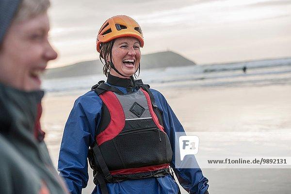 Mittlere erwachsene Frau mit Helm und Schwimmweste  lachend