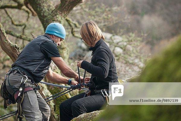 Erwachsener Mann und mittlere erwachsene Frau beim Anlegen von Kletterseilen