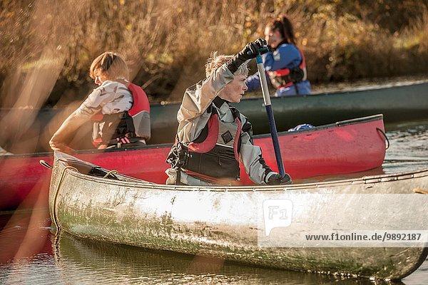 Mittlere erwachsene Frau  die sich im Kanu umdreht