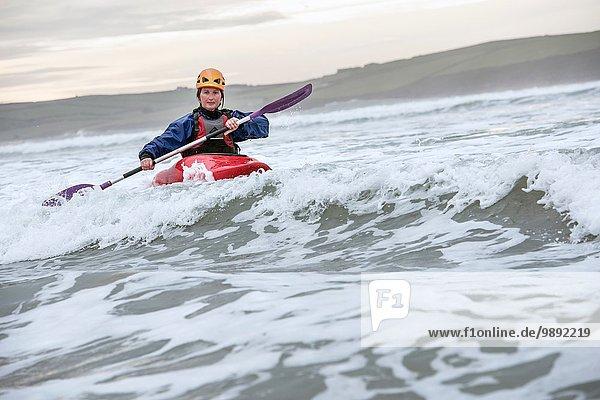 Mittlere erwachsene Frau Seekajakfahren