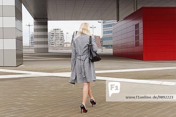 Businesswoman  walking outdoors  rear view