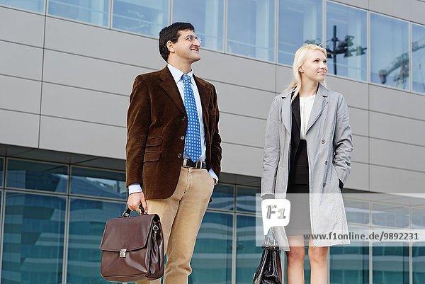Geschäftsmann und Geschäftsfrau  zusammen stehend  im Freien