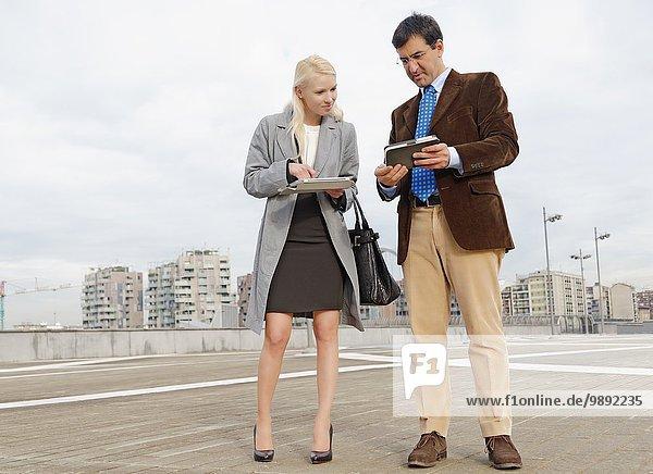 Geschäftsmann und Geschäftsfrau im Freien  mit digitalen Tabletts  Informationsaustausch