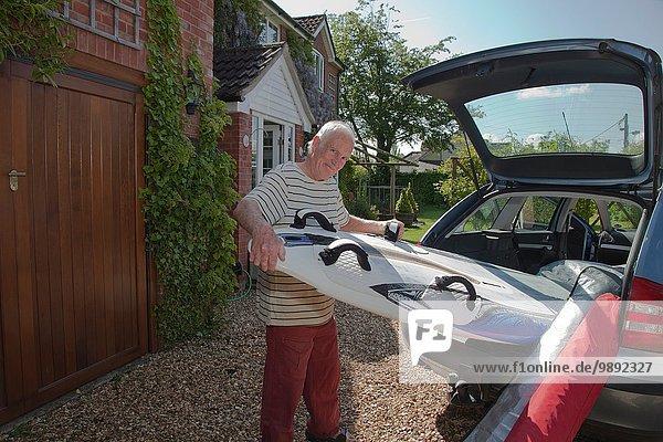 Senior Mann  der das Surfbrett aus dem Kofferraum entfernt.
