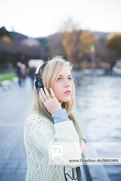 Young woman looking up whilst listening to headphones on lakeside  Como  Italy