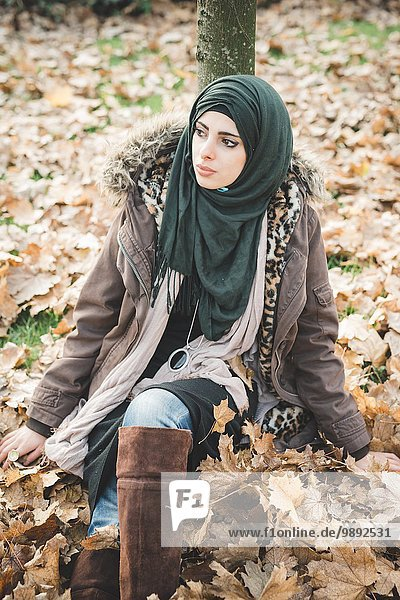 Young woman sitting in park amongst autumn leaves