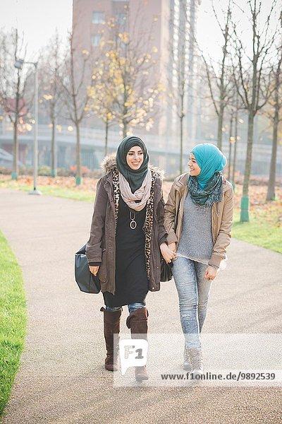 Zwei junge Frauen plaudern beim Bummeln im Park