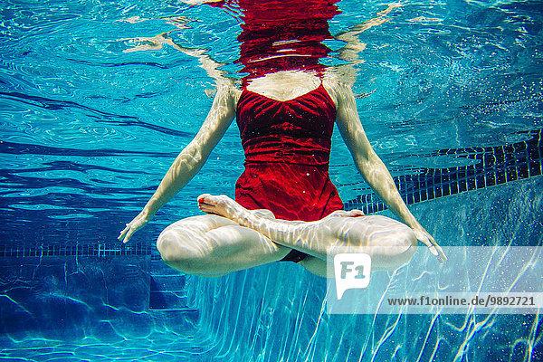 Reife Frau in rotem Kleid  Beine gekreuzt  Unterwasseransicht  niedriger Schnitt