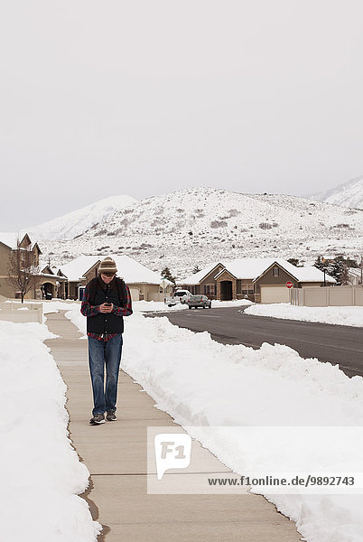 Teenage boy reading smartphone texts whilst walking path in snow covered village