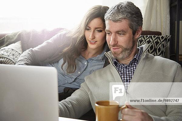 Junges Paar trinkt Kaffee und schaut auf den Laptop