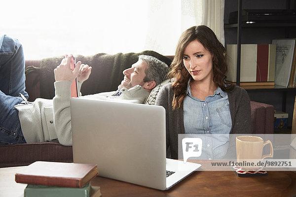 Junges Paar im Wohnzimmer mit Laptop und digitalem Tablett