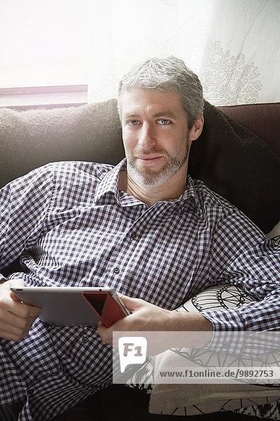 Porträt eines jungen Mannes  der sich auf dem Wohnzimmersofa mit Hilfe eines digitalen Tabletts hinlegt.