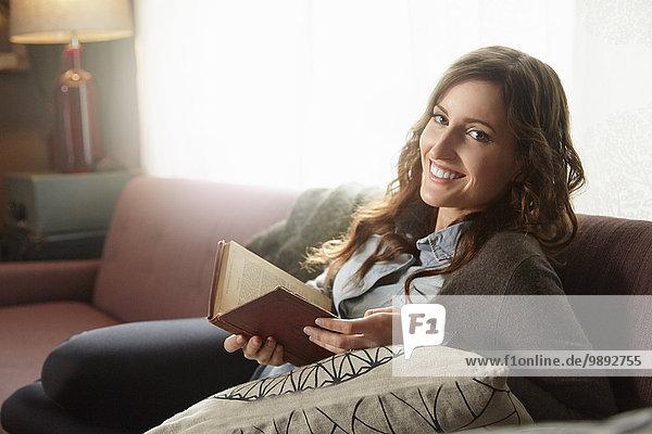 Porträt einer jungen Frau beim Lesen auf dem Wohnzimmersofa
