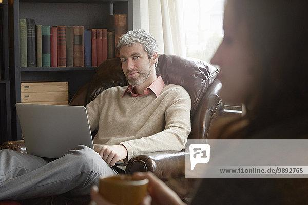 Junger Mann schaut seitwärts auf Freundin im Wohnzimmer