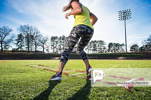 Sportlerinnen-Training mit Wendigkeitsleiter auf dem Sportplatz