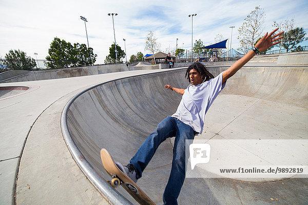 Junger Mann beim Skateboarden auf der Skateboard-Park-Wand