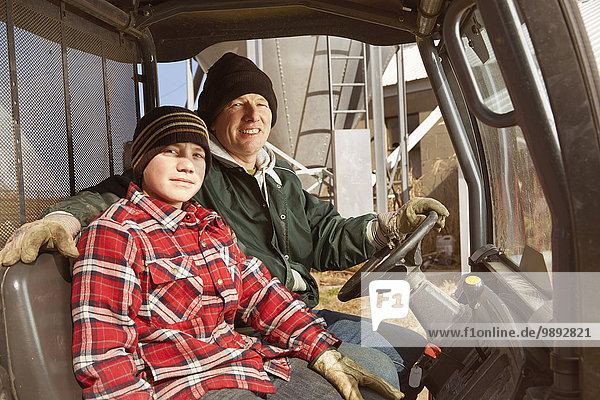 Portrait of father and son dairy farmers in lorry