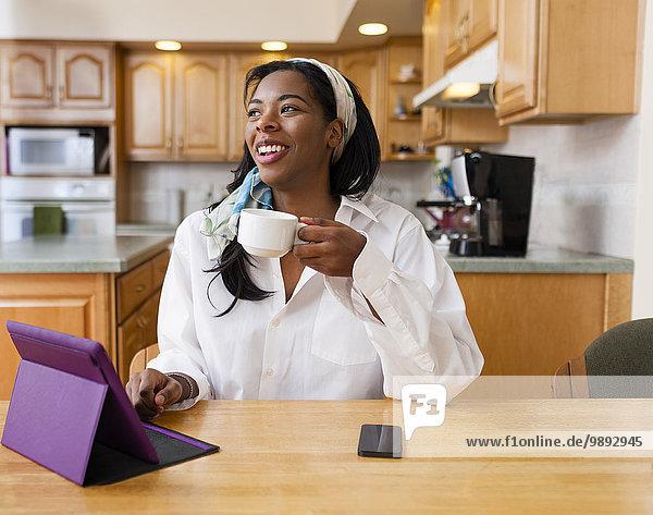 Junge Frau mit digitalem Tablett am Küchentisch