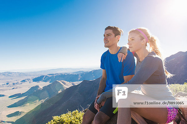 Trail running couple looking out at landscape on Pacific Crest Trail  Pine Valley  California  USA