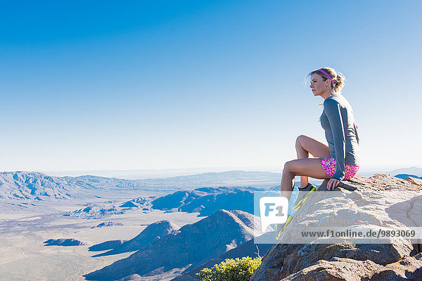 Young female trail runner gazing from rock on Pacific Crest Trail  Pine Valley  California  USA