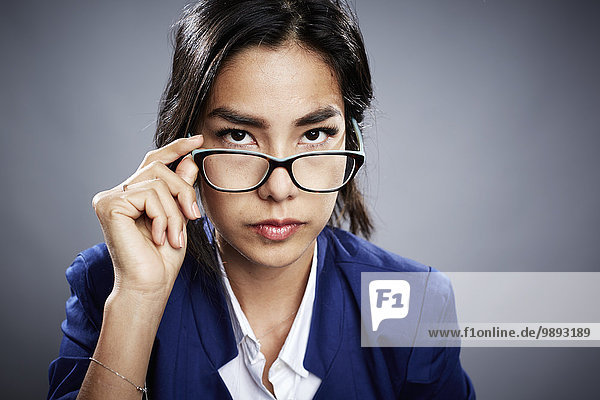 Portrait of young woman looking over eyeglasses