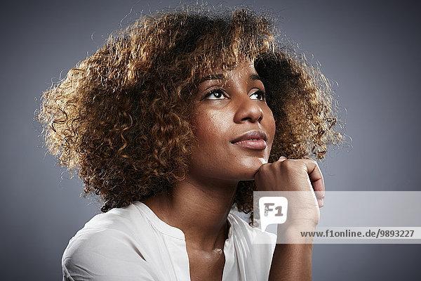 Porträt einer jungen Frau  Hand am Kinn  aufblickend