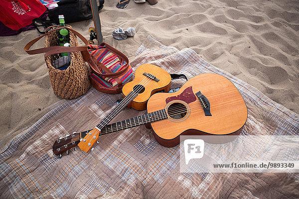 Gitarren und Taschen auf Picknickdecke am Sandstrand