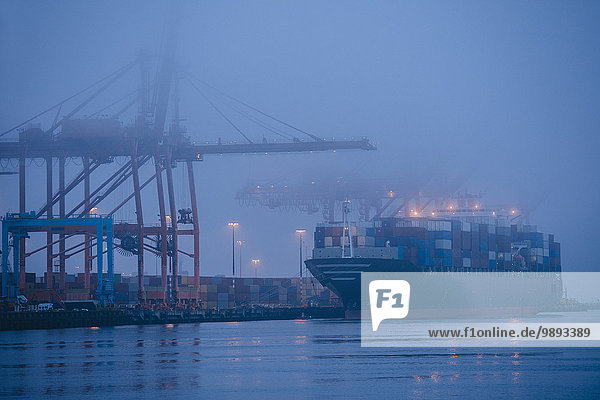 Misty view of cargo ship and cranes on waterfront at night  Seattle  Washington  USA