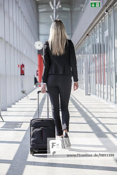 Rückansicht Eingangshalle Geschäftsfrau ziehen Gepäck modern