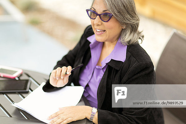 Mature businesswoman sitting at table  going through document