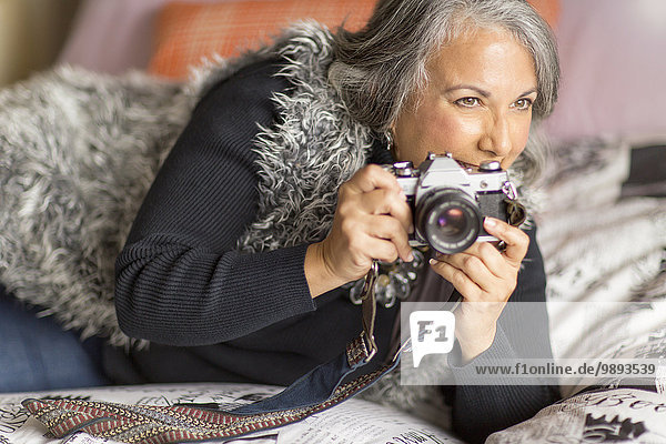 Reife Frau entspannt auf dem Bett  hält Spiegelreflexkamera