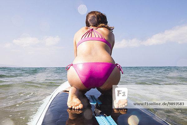 Frau kniend auf dem Surfbrett  Rückansicht