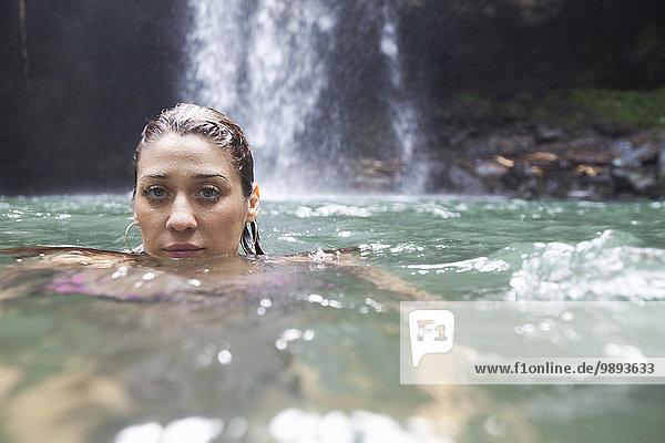 Schwimmende Frau  Wasserfall im Hintergrund