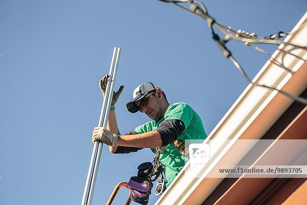 Solarmodulmonteur auf dem Dach des Hauses