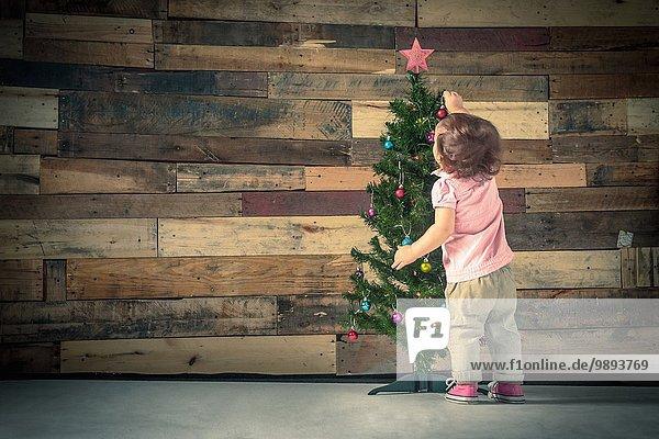 Kleines Mädchen schmückt Weihnachtsbaum