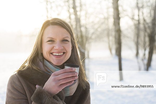 Young woman in warm clothing drinking hot tea outdoors