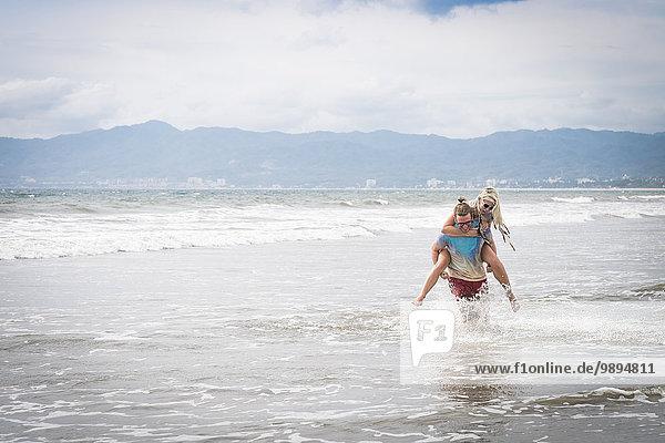 Mexiko  Riviera Nayarit  junger Mann  der seiner Freundin ein Huckepack gibt.
