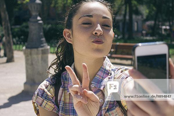 Junge Frau  die einen Selfie mit Smartphone nimmt