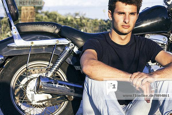 Spanien  Madrid  junger Mann bei Sonnenuntergang neben seinem Motorrad sitzend