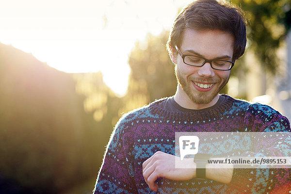 Porträt eines lächelnden jungen Hipsters mit Blick auf seine Smartwatch