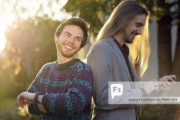 Zwei lachende Hipster mit Smartwatch und Smartphone
