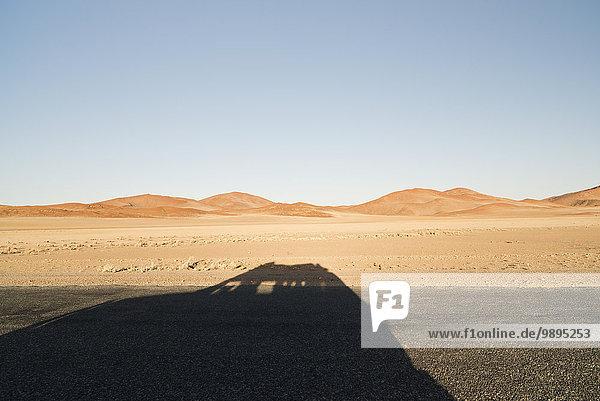 Namibia  Namib Wüste  Namib Naukluft Park  Schatten eines durch Sossusvlei fahrenden Autos